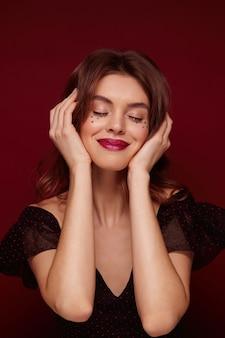 Довольная привлекательная молодая шатенка с праздничным макияжем в элегантном черном топе с красными точками, позируя на бордовом фоне, красиво улыбаясь с закрытыми глазами