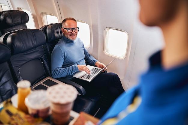 Довольный бородатый бизнес улыбается стюардессе