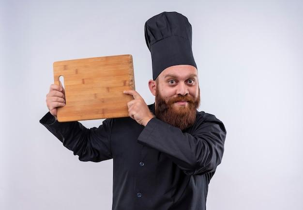 Un uomo felice chef barbuto in uniforme nera che mostra il bordo della cucina in legno su un muro bianco
