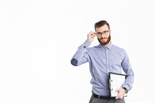 Довольный бородатый элегантный мужчина в очках держит буфер обмена и смотрит