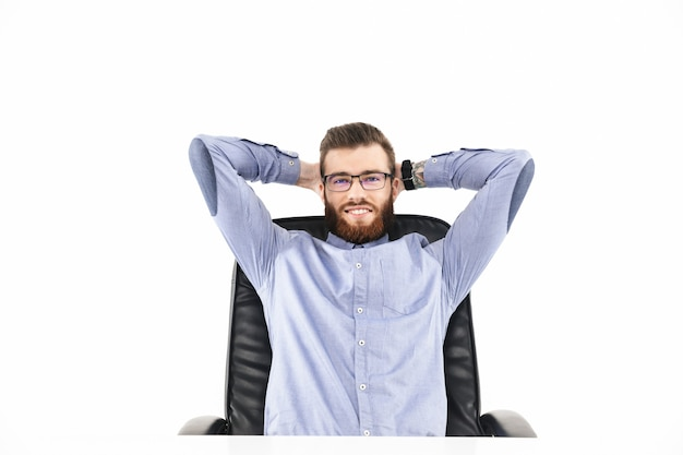 Довольный бородатый элегантный мужчина в очках смотрит и наслаждается, сидя за столом