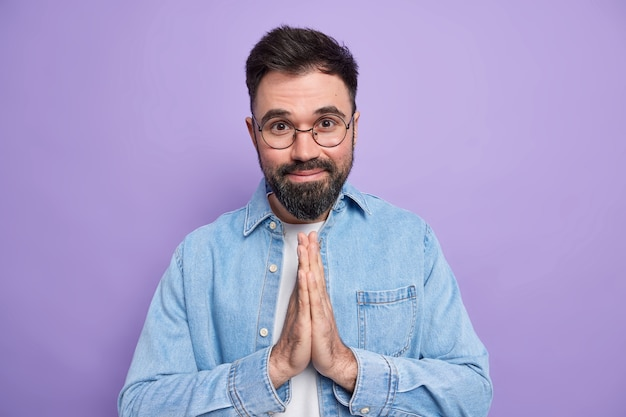 Pleased bearded european man keeps palms pressed together asks for help wears round spectacles denim shirt has happy expression
