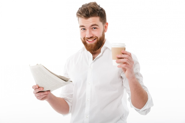 Pleased bearded man in business clothes holding newspaper