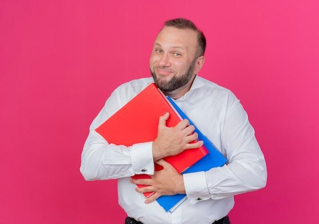 Soddisfatto uomo barbuto che indossa una camicia bianca che tiene le cartelle sorridendo allegramente sul rosa