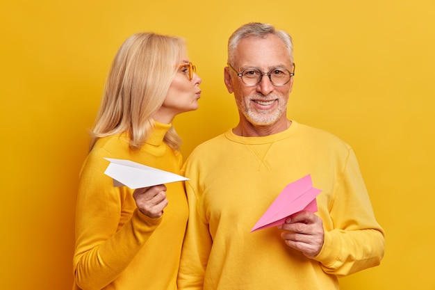 Pleased beatded grey haired man gets kiss from wife pose next to each other hold handmade paper planes isolated over yellow wall