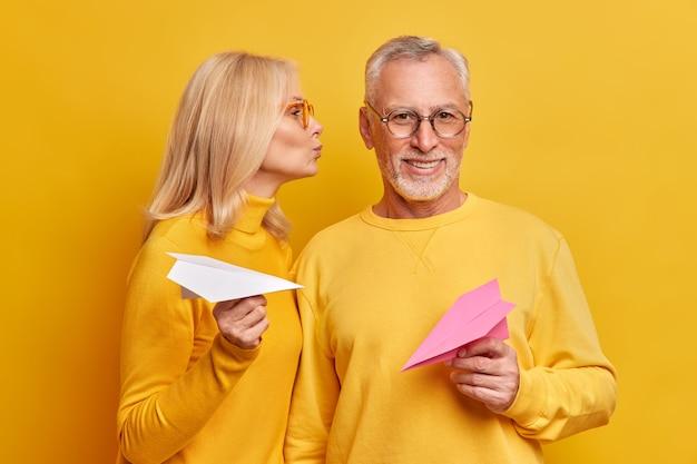 喜んで殴られた白髪の男が隣同士の妻のポーズからキスを取得黄色の壁に隔離された手作りの紙飛行機を保持します