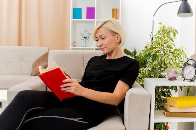 Felice bella bionda donna russa sdraiata sulla poltrona tenendo e guardando il libro all'interno del soggiorno