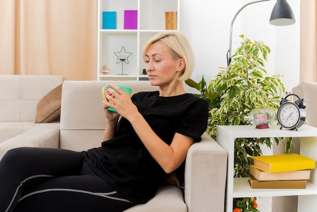 リビングルーム内のカップを保持し、見て肘掛け椅子に横たわっている美しい金髪のロシアの女性を喜ばせる