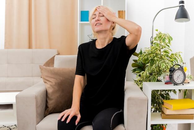 満足している美しい金髪のロシアの女性は、リビングルームの中で額に手を置いて肘掛け椅子に座っています