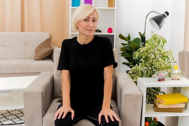 満足している美しい金髪のロシアの女性は、リビングルーム内のカメラを見て足に手を置いて肘掛け椅子に座っています