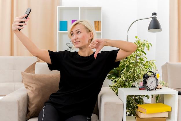 기쁘게 아름 다운 금발 러시아 여자는 거실 내부에서 셀카를 복용 카메라를보고 아래로 안락의 자 엄지 손가락에 앉아