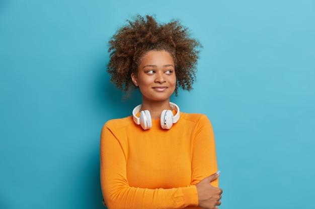 La bella adolescente femmina soddisfatta con i capelli ricci tiene le mani incrociate sul petto indossa le cuffie sul collo e guarda felicemente da parte.