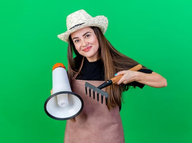 Довольная красивая девушка-садовник в униформе в садовой шляпе, держащая громкоговоритель с граблями, изолированными на зеленом