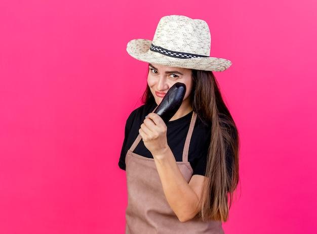 Довольная красивая девушка-садовник в униформе в садовой шляпе, протягивая баклажаны, изолированные на розовом
