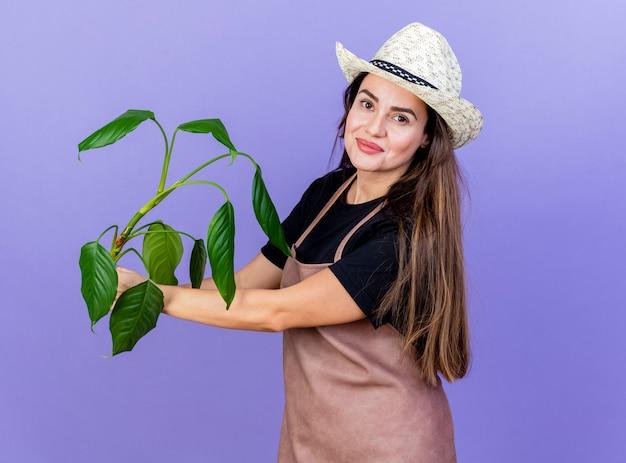 Довольная красивая девушка-садовник в униформе в садовой шляпе, протягивая растение сбоку, изолированное на синем