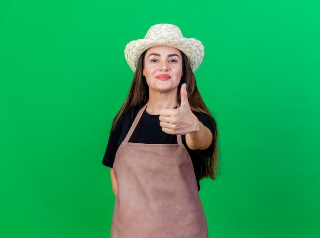 緑の背景に分離された親指を示すガーデニング帽子を身に着けている制服を着た美しい庭師の女の子を喜ばせる