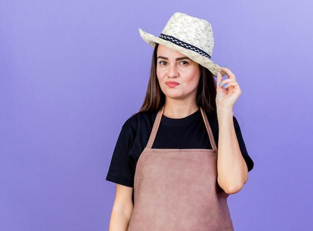 Felice bella ragazza giardiniere in uniforme che indossa il cappello da giardinaggio ha afferrato il cappello isolato su sfondo blu
