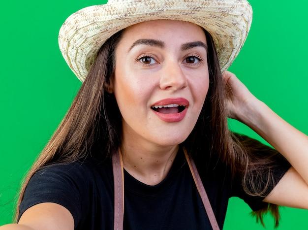 Felice bella ragazza giardiniere in uniforme che indossa il cappello da giardinaggio tenendo la fotocamera e mettendo la mano sulla testa isolata sul verde