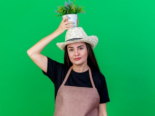 Lieta bella ragazza giardiniere in uniforme che indossa cappello da giardinaggio tenendo il fiore in vaso di fiori sulla testa isolato su sfondo verde