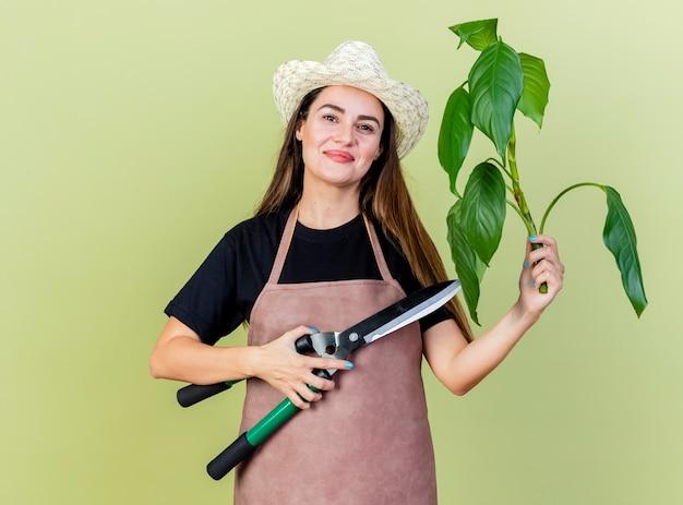 Lieta bella ragazza giardiniere in uniforme che indossa il cappello da giardinaggio che tiene in pianta con clippers isolato su sfondo verde oliva