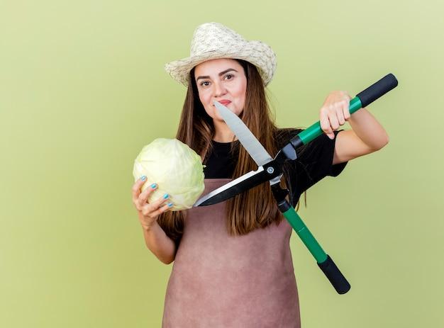 Lieta bella ragazza giardiniere in uniforme che indossa cappello da giardinaggio cercando di tagliare il cavolo con i clippers isolato su sfondo verde oliva
