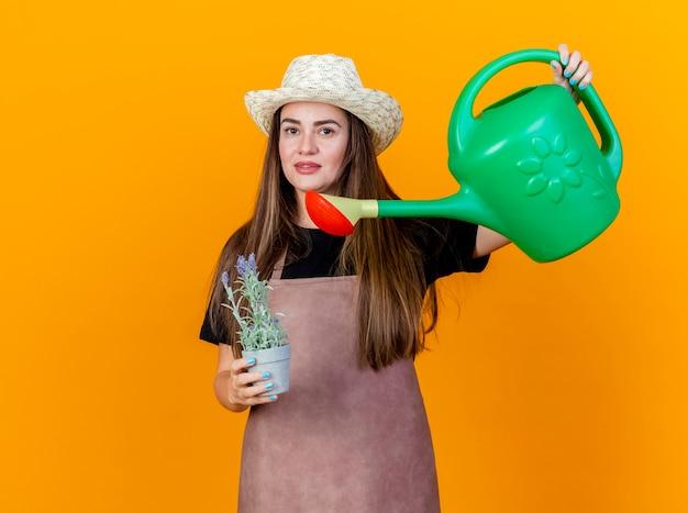 Lieta bella ragazza giardiniere che indossa uniforme e cappello da giardinaggio holding e irrigazione fiore in vaso di fiori con annaffiatoio isolato su sfondo arancione