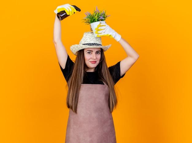 Felice bella ragazza giardiniere che indossa uniforme e cappello da giardinaggio