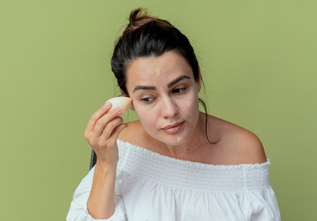 Bella ragazza soddisfatta che applica fondotinta con spugna isolata sulla parete verde