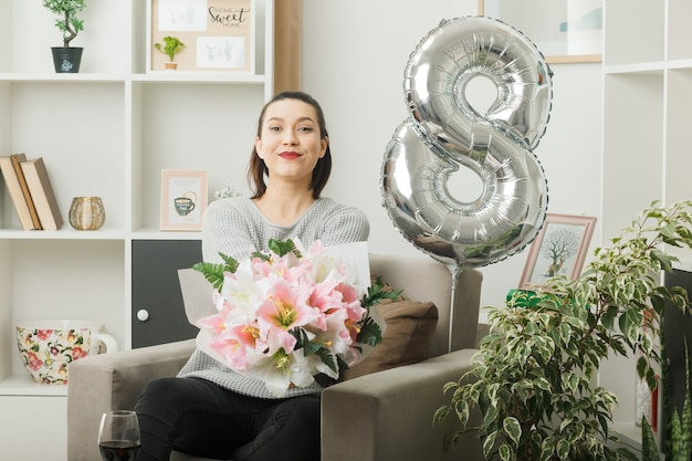 Bella ragazza contenta il giorno delle donne felici che tiene il mazzo seduto sulla poltrona in soggiorno