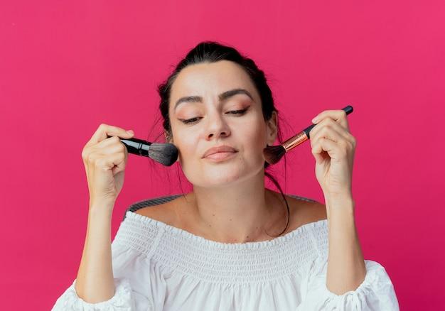 기쁘게 아름다운 소녀 보유하고 분홍색 벽에 고립 된 얼굴에 메이크업 브러쉬를 넣습니다 무료 사진