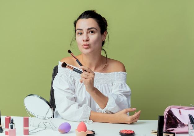 La bella ragazza soddisfatta si siede al tavolo con gli strumenti di trucco che tengono i pennelli di trucco isolati sulla parete verde