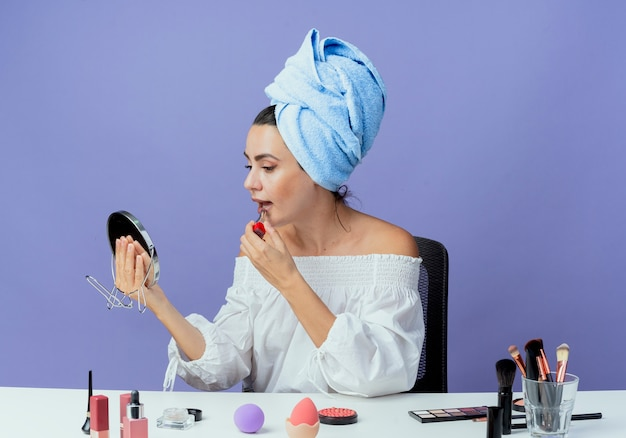 Pleased beautiful girl wrapped hair towel sits at table with makeup tools holding and applying lipstick looking at mirror isolated on purple wall
