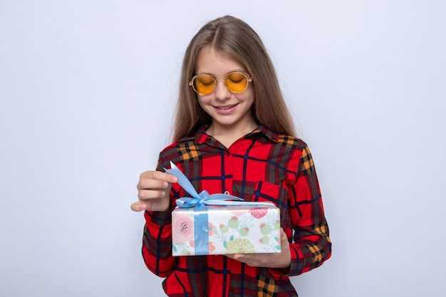 Pleased beautiful little girl wearing red shirt and glasses holding and looking at present