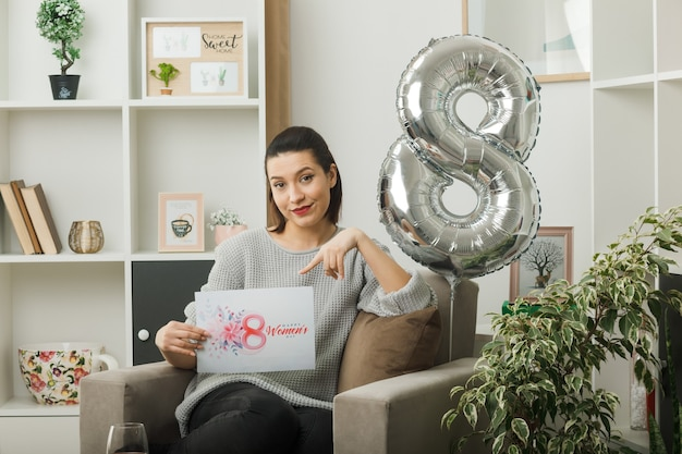 Pleased beautiful woman on happy women day holding and points at postcard sitting on armchair in living room
