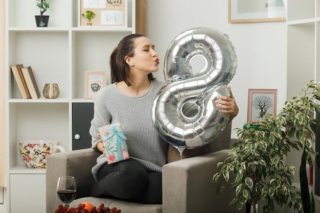 행복한 여성의 날에 행복한 아름다운 여성이 거실에 있는 안락의자에 앉아 있는 8번 풍선을 들고 있다