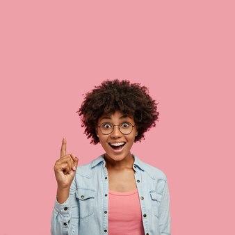 ピンクの壁にポーズをとって喜んで美しい女性