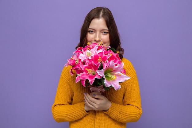 青い壁に分離された花束を保持している幸せな女性の日に美しい少女を喜ばせる