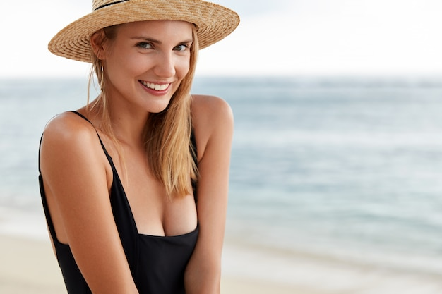Pleased beautiful young woman with attractive in good mood, wears summer hat and black swimming suit, poses against beautiful ocean view. female spends time in resort island