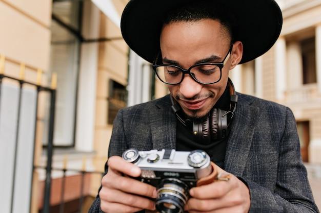 카메라와 함께 길을 걷고 헤드폰에 기쁘게 흑인 남자. 도시 거리에 서있는 어두운 재킷에 호기심이 남성 아프리카 사진 작가의 야외 사진.