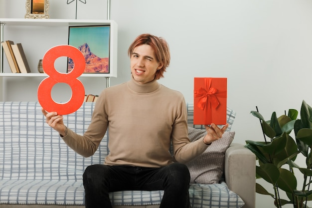 Pleased blinked handsome guy on happy women day holding number eight with present sitting on sofa in living room