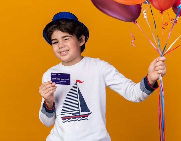 Pleased blinked little boy wearing blue party hat holding balloons with credit card isolated on orange wall