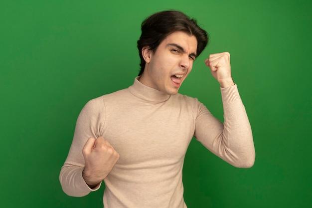 緑の壁に分離されたはいジェスチャーを示す喜んで点滅した若いハンサムな男