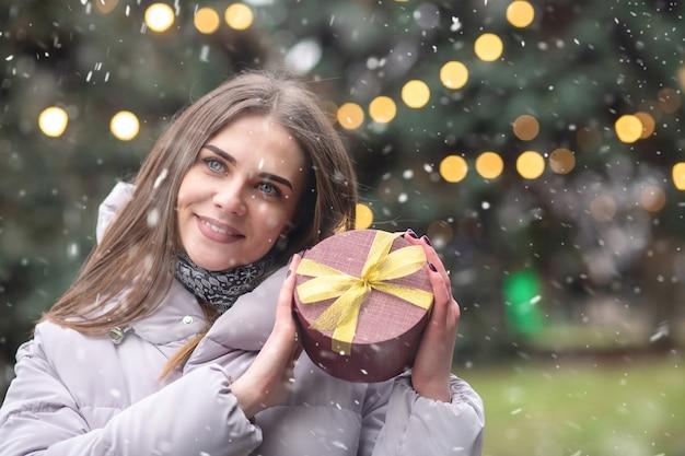 喜んでいる金髪の女性は、降雪時に新年の装飾が施された通りでガートボックスを保持している灰色のコートを着ています。空きスペース