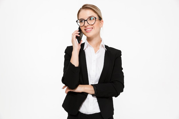 Pleased blonde business woman in eyeglasses talking by the phone and looking away over white