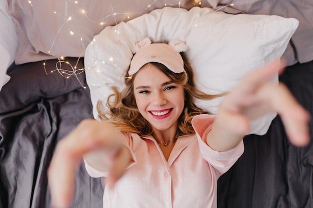 어두운 시트에 누워 기쁘게 금발 소녀. 침대에서 포즈 핑크 eyemask에 웃는 명랑 한 아가씨의 실내 오버 헤드 사진.