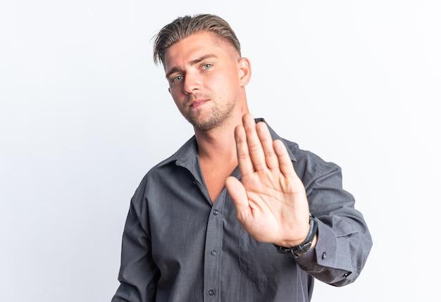 一時停止の一時停止の標識を身振りで示す金髪のハンサムな男を喜ばせる