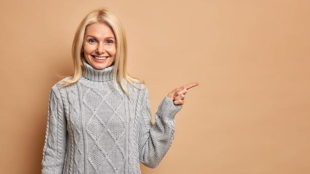 주름을 가진 기쁘게 금발 중간 나이 든된 여자는 복사 공간을 가리키는 따뜻한 회색 스웨터를 착용