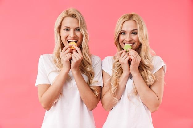 Довольные близнецы-блондинки в футболках едят пирожные и смотрят спереди через розовую стену