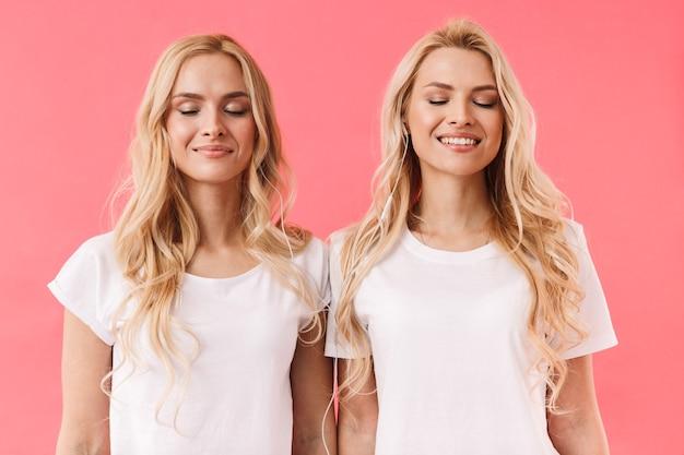 ピンクの壁に目を閉じて音楽を聴いているtシャツを着て喜んでいる金髪の双子