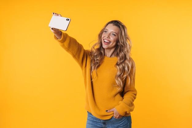 Довольная блондинка в теплом свитере улыбается и делает селфи на смартфоне, изолированном над желтой стеной